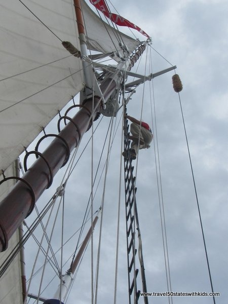 Crew member climbing the ladder on the Tall Ship Manitou